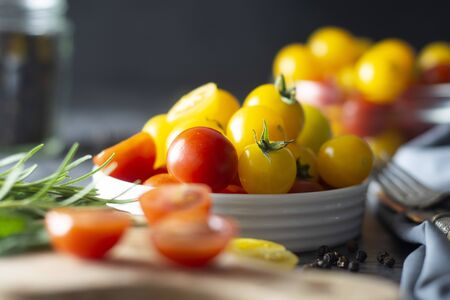 Organic yellow and red tomatoes in plate over dark background.