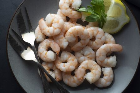 Fresh shrimps in plate over dark background. Healthy food. Top view.