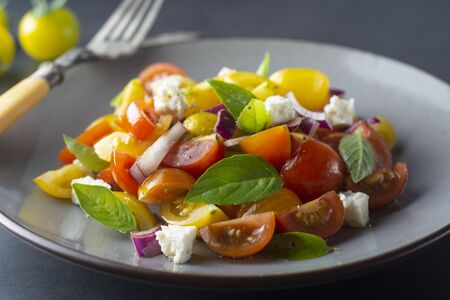 Colorful cherry tomatoes and basil salad on a plate, dark background. Healthy food.