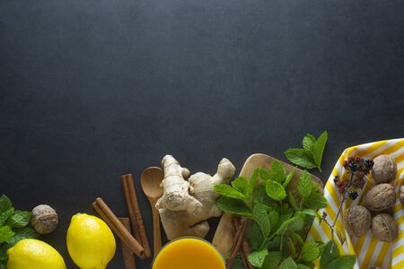 Ginger, lemons and mint leaves on dark background. Ginger tea, drink ingredients, cold and autumn. Copy space.