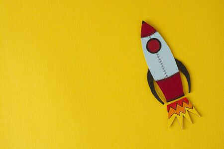 Start up business concept. Boost or increase incomes, salary. Drawn rocket on colorful yellow background. Copy space for text.