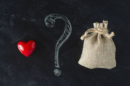 Love or money choise. red heart and a bag with money. Chackboard wih question mark. Make right decision. Stockfoto