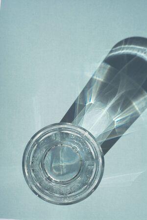Een glas zuiver water onder zonlicht met diepe stijlvolle schaduwen op blauwe achtergrond kopieerruimte voor tekst