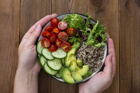 Healthy food. Womans hand holding budha bowl with quinoa, avocado, cucumber, salad, tomatoe, olive oil. Clean eating, diet food.