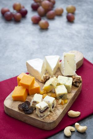 Various different types of cheese slices, cheese mix on wooden cutting board. Camembert, parmesan, brie cheese. Copy space.