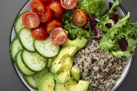 Close up of budha bowl with quinoa, avocado, cucumber, salad, tomatoe, olive oil Clean eating diet food