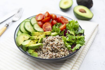 Healthy food. budha bowl with quinoa, avocado, cucumber, salad, tomatoe, olive oil Clean eating diet food. Bright background.