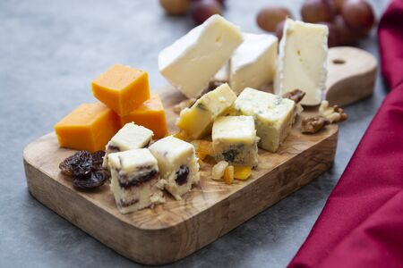 Various different types of cheese slices, cheese mix on wooden cutting board. Camembert, parmesan, brie cheese.