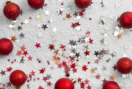 Abstract glittered Christmas  with red baubles over white board.