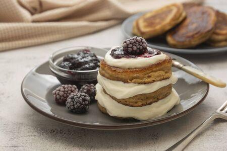 Tortitas con frutos rojos y mermelada. tortitas caseras, veganas con crema y mermelada de frutas en plato. Foto de archivo