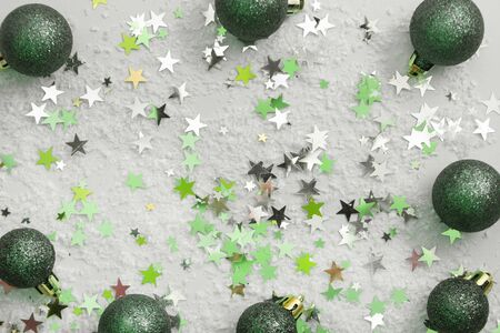 Abstract glittered Christmas background with green baubles over white board. Copy space for text.