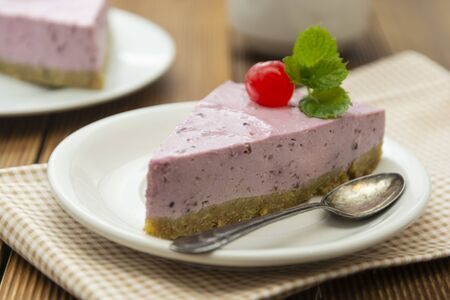 Cheesecake slice with berries and coffee cup, pink cheesecake on wooden background, dessert or breakfast. Sweet food. Фото со стока