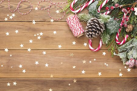 Christmas background with a red and white candie canes, fir branches, winter decoration, star shapes glitter. Copy space.