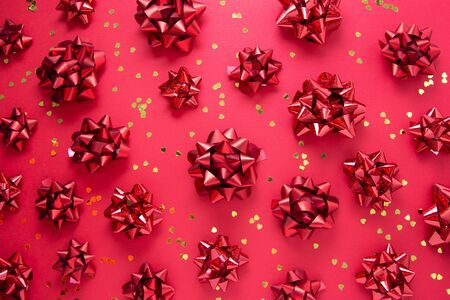 Red bows and heart shaped golden glitter, over red background, flat lay. Party, birthday, Christmas or Valentines Day pattern.
