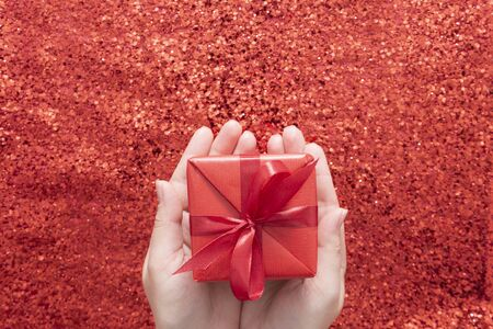 Female hands holding gift box over red glitter sparkling background, copy space. Valentines Day, Christmas.