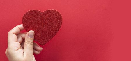 Top view of female hands holding a sparkling glowing heart isolated over flat lay background, copy space for text.