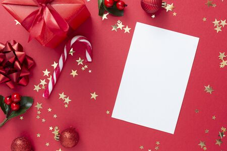 Christmas background with blank paper, red gift box with ribbon bow on red background and golden sparkling confetti, candy cane, baubles