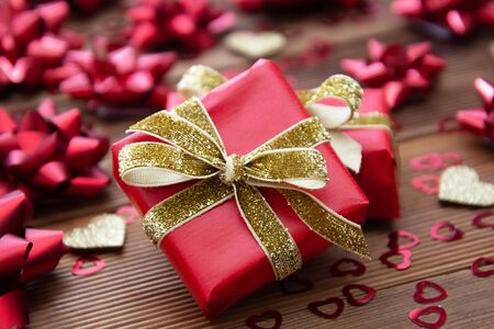 Red gift box with bows, on wooden background. Copy space. Valentines day, Birthday, Christmas