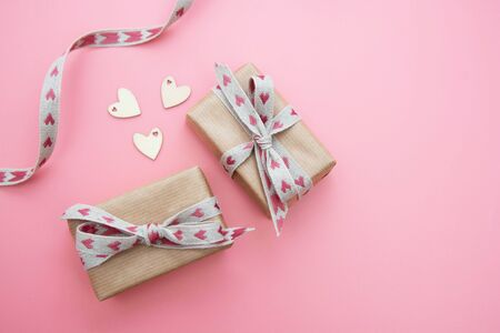 Gift box wrapped in kraft paper and bow, on pink background. Valentines Day, Birthday, Party mock up. Stock Photo