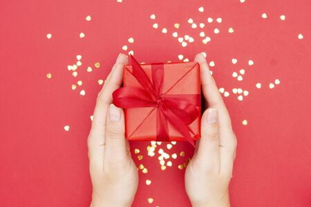 Top view of female hands holding gift box with red ribbon bow isolated over flat lay background, copy space for text Stock Photo