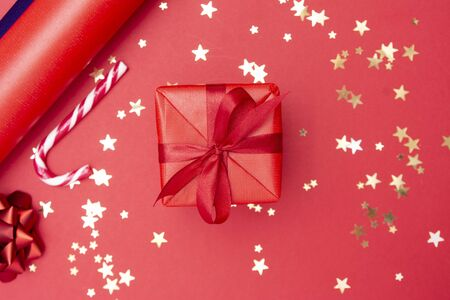 Christmas background, red gift box with ribbon bow on red background and golden sparkling confetti, candy cane, baubles