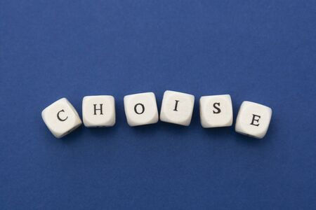 Choise word, lettering written on wooden blocks over blue background. Copy space.
