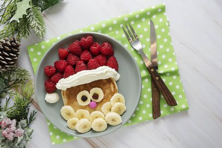 Fun food for kids. Christmas Santa pancake with raspberry and banana for children menu, top view with copy space for text. Stock Photo
