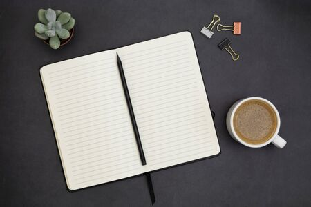 Open notebook with empty page and coffee cup. Table top, work space on dark background. Abstract flat lay.