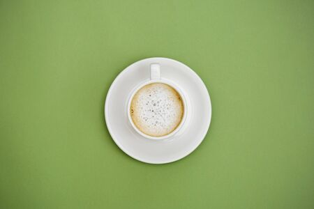 Top view hot latte coffee in white cup. Isolated on green background. Copy space for text. Banco de Imagens