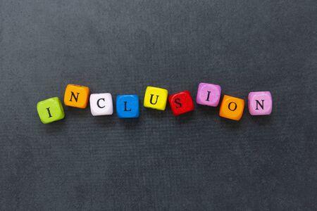 Einschlusstext von mehrfarbigen Würfeln auf dunklem Hintergrund. Inklusives soziales Konzept. Beschriftung.