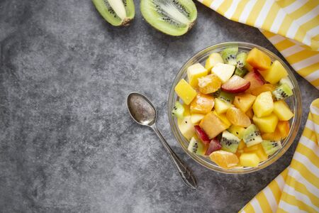 Fresh fruits salad flat lay - mango, citrus, kiwi fruit, plum and persimmon. Copy space for text.