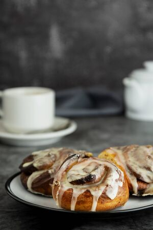 Cinnamon danish bun or cinnabons on dark
