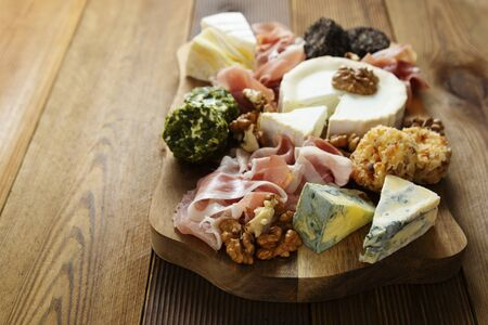 Cheese plate, various types of cheeses, grapes, walnuts and honey and prosciutto. Wooden cutting board, wooden table.