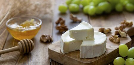 White, round cheeses on wooden background with honey and grapes. Dark food photography. Banner. 스톡 콘텐츠