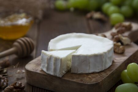 White, round cheeses on wooden background with honey and grapes. Dark food photography.