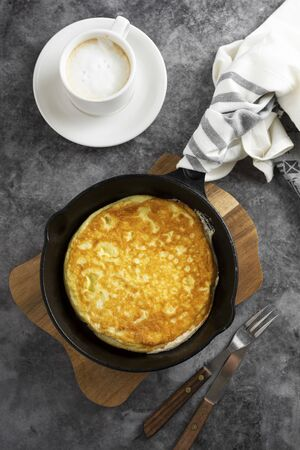 Omelette in frying pan and cup of coffee. Foto de archivo