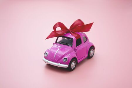 Corby, U.K. February 7, 2020. Miniature pink toy car with red ribbon bow, on pink background. Reklamní fotografie