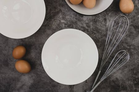 Dark baking background with eggs, whisk, eggshell and white plates. Copy space, top view for text. Banco de Imagens