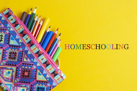 Homeschooling text over yellow background with colorful pencils. Learn from home.
