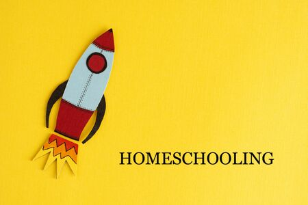 Homeschooling text with rocket over yellow abstract background. Learn from home. Quarantine education. 版權商用圖片