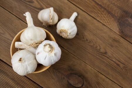 Isolated garlic whole on wooden background. Cooking ingredients, copy space Reklamní fotografie
