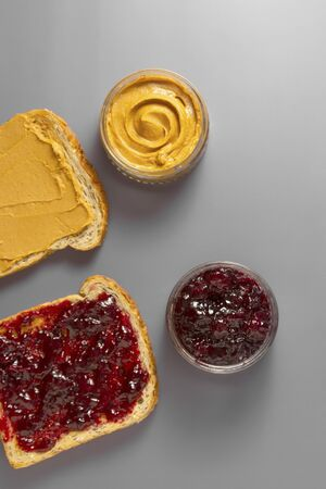 Sandwiches or bread toast with peanut butter and fruit jelly. Flat lay.