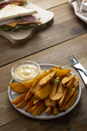 Roasted potato chips with club sandwich. Wooden background, copy space for text.