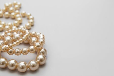 White pearls on the gray background, isolated. Abstract fashion background. Copy space.