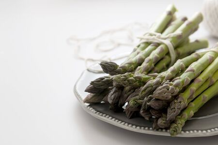 Fresh asparagus, grey plate over white background