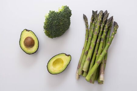 Green vegetables - asparagus, avocado and broccoli. Fresh vegetable mix. Healthy eating concept. Stock Photo