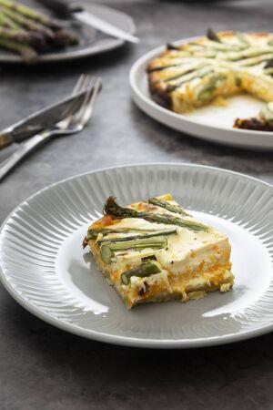 Slice of asparagus tart. Homemade pie filled with fresh asparagus. Vegetarian food.