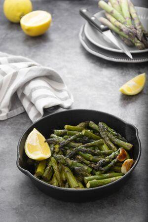 Fresh green roasted asparagus in black iron pan. Healthy, vegan foods