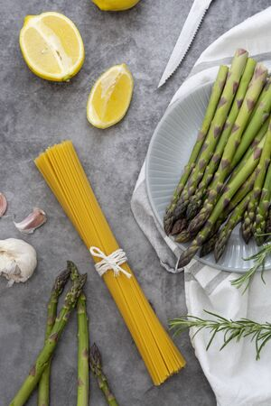 Abstract food background with raw pasta and asparagus on a dark background, cooking healthy foods