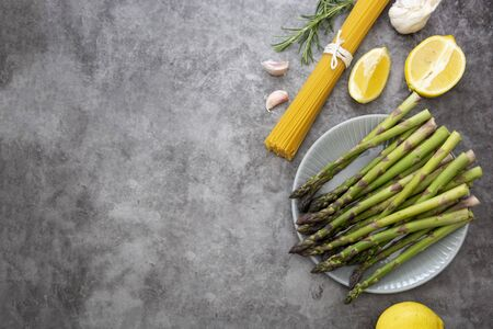 Raw pasta and asparagus on a dark background, cooking healthy foods